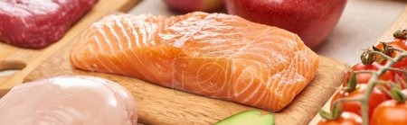 Photo for Panoramic shot of raw salmon fillet on wooden cutting board near meat and tomatoes - Royalty Free Image