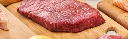 Photo for Panoramic shot of raw meat steak on wooden cutting board - Royalty Free Image