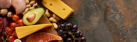 Photo for Panoramic shot of fresh vegetables and fruit with raw fish and poultry on wooden cutting board near cheese and peanuts on marble surface - Royalty Free Image