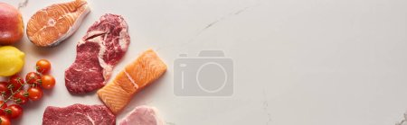 Photo for Panoramic shot of raw meat, fish and poultry near tomatoes, lemon and apple on marble surface with copy space - Royalty Free Image