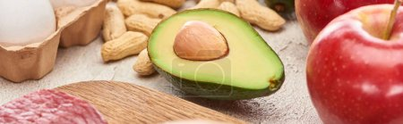 Photo for Panoramic shot of half of avocado on marble surface near peanuts, apple and part of egg - Royalty Free Image