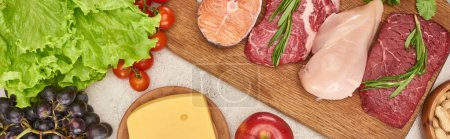Photo for Panoramic shot of wooden cutting board with raw fish, meat and poultry near tomatoes, lettuce, cheese and apple on marble surface - Royalty Free Image