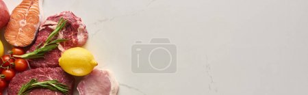 Photo pour Tir panoramique de poisson cru, viande avec des rameaux de romarin près du citron et tomates sur la surface de marbre avec l'espace de copie - image libre de droit