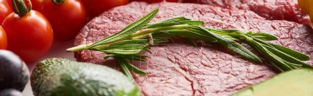 Photo for Panoramic shot of raw near steak with rosemary twig on it near cherry tomatoes - Royalty Free Image