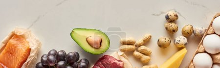 Photo for Panoramic shot of half of avocado, peanuts, quail and chicken eggs, cheese, grape, raw meat and fish on marble surface with copy space - Royalty Free Image