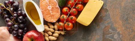 Photo for Panoramic shot of raw salmon steak near grape, tomatoes, peanuts, apple, olive oil and cheese on marble surface - Royalty Free Image