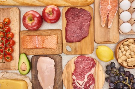 Photo for Top view of assorted meat, poultry, fish, eggs, fruits, vegetables, cheese and baguette on wooden cutting boards - Royalty Free Image
