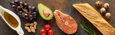 Photo for Panoramic shot of raw salmon steak near vegetables, grape, quail eggs, peanuts, baguette and olive oil on marble surface - Royalty Free Image