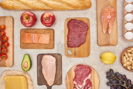 Photo for Top view of assorted meat, poultry, fish, eggs, fruits, vegetables, cheese and baguette on wooden cutting boards on marble surface - Royalty Free Image