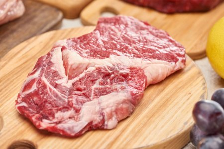 Photo for Close up view of raw meat on light wooden cutting board - Royalty Free Image