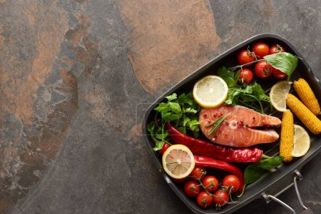Photo for Top view of uncooked salmon with vegetables, lemon and herbs in grill pan - Royalty Free Image