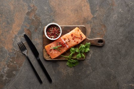 Photo for Top view of raw fresh salmon with peppercorns, parsley on wooden cutting board near cutlery - Royalty Free Image