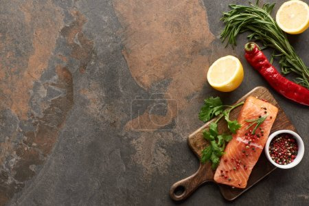 Photo for Top view of raw salmon with greenery and lemon on wooden cutting board - Royalty Free Image