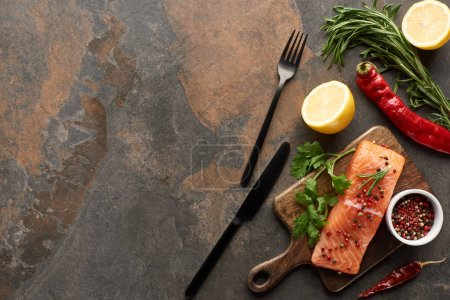 Photo for Top view of raw fresh salmon with herbs and lemon on wooden cutting board near cutlery and chili peppers - Royalty Free Image