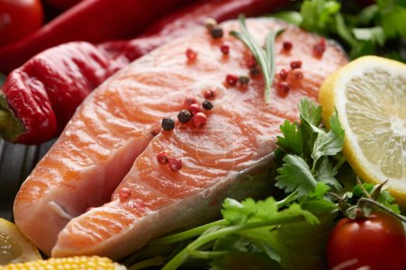 Photo pour Fermer la vue vers le haut du bifteck cru de saumon avec des épices, des légumes et de la verdure - image libre de droit