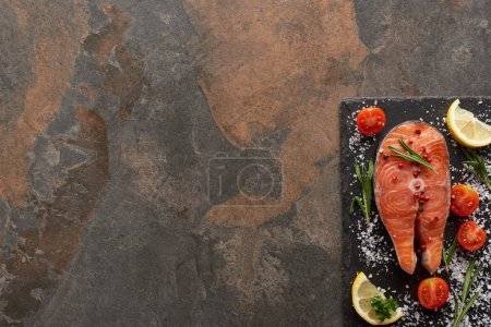 Photo for Top view of raw salmon with seasoning and tomatoes on stone board - Royalty Free Image