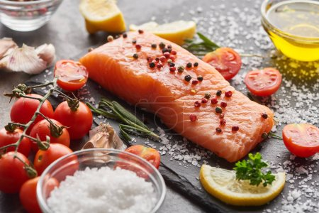Photo for Raw salmon with seasoning and tomatoes on stone board with salt - Royalty Free Image