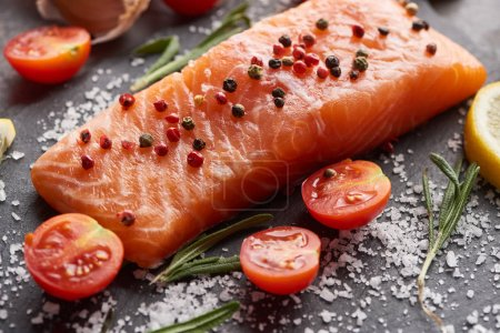 Photo for Raw salmon with salt and tomatoes on stone board - Royalty Free Image