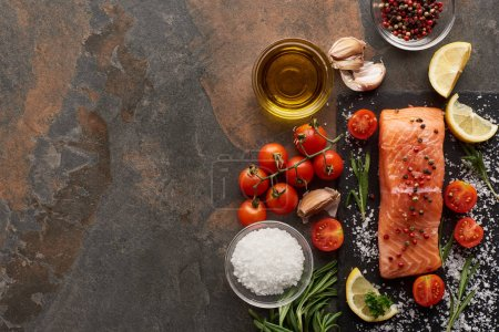 Photo for Top view of raw salmon with seasoning, oil, garlic and tomatoes on stone surface - Royalty Free Image