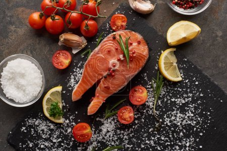 Photo for Top view of raw salmon with salt, lemon and tomatoes on stone board - Royalty Free Image