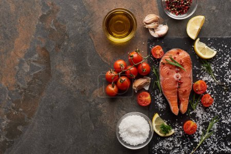 Photo for Top view of raw salmon with salt, rosemary and tomatoes on stone board - Royalty Free Image