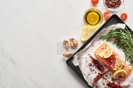 Photo for Top view of raw salmon steak with lemon, rosemary and chili peppers on oven tray with salt near garlic and oil - Royalty Free Image