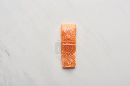 Photo for Top view of uncooked fresh salmon steak on white marble surface - Royalty Free Image