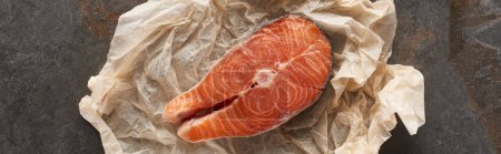 Photo for Top view of raw salmon steak on bakery paper on stone table, panoramic shot - Royalty Free Image