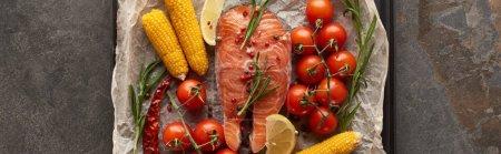 Photo pour Coup panoramique de steak de saumon cru avec tomates, maïs, romarin, citron sur papier de boulangerie sur plateau de four - image libre de droit