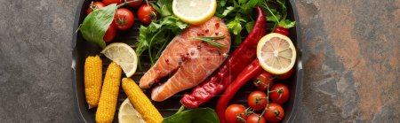 top view of uncooked salmon steak with vegetables, lemon and herbs in grill pan, panoramic shot