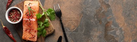 Photo for Top view of raw fresh salmon with peppercorns, parsley on wooden cutting board near cutlery and chili peppers, panoramic shot - Royalty Free Image