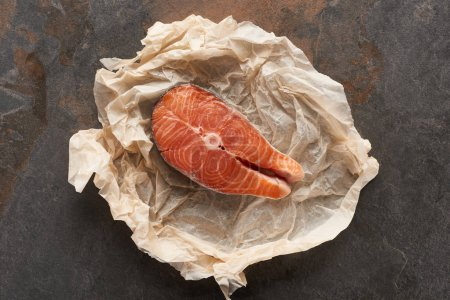 Photo for Top view of raw salmon steak on bakery paper on stone table - Royalty Free Image