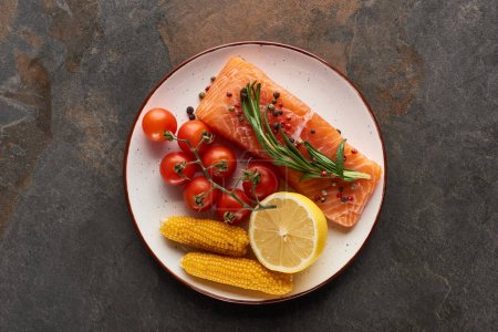 Photo for Top view of raw salmon steak with tomatoes, corn, lemon, rosemary and pepper on plate - Royalty Free Image