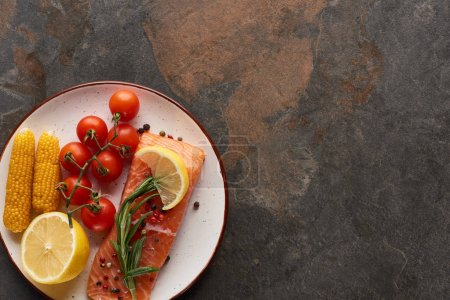Photo for Top view of uncooked salmon steak with tomatoes, corn, lemon, rosemary and pepper on plate - Royalty Free Image