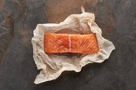Photo for Top view of uncooked salmon steak on bakery paper on stone table - Royalty Free Image