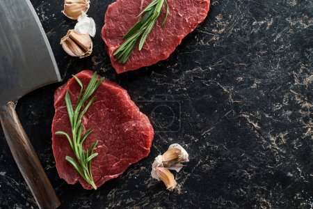 Photo for Top view of raw beef steaks with rosemary twigs and garlic cloves near sharp knife on black marble surface - Royalty Free Image