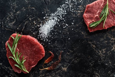 Photo for Top view of raw beef steaks with rosemary twigs near dried cayenne peppers and scattered salt on black marble surface - Royalty Free Image