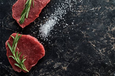 Photo for Top view of raw beef steaks with rosemary twigs on black marble surface with scattered salt crystals - Royalty Free Image