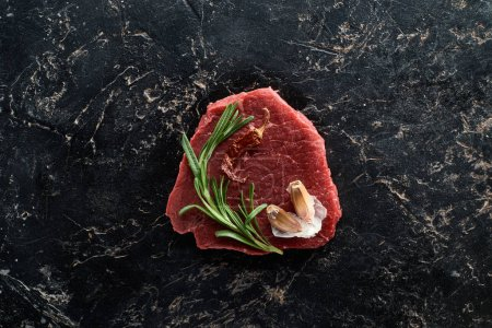 Photo for Top view of raw beef steak with rosemary and garlic on black marble surface - Royalty Free Image