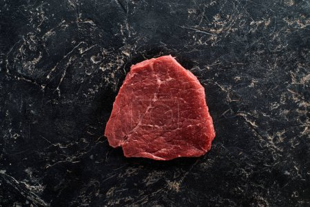 Photo for Top view of raw meat steak on black marble surface - Royalty Free Image