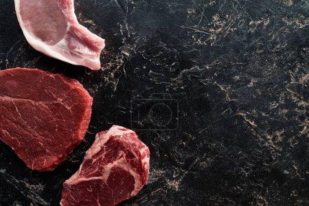 Ansicht von rohen Rind- und Schweinefleischteilen auf schwarzer Marmoroberfläche