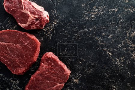 Photo for Top view of raw beef parts on black marble surface - Royalty Free Image