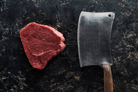 Photo for Top view of butcher knife near raw beef steak on black marble surface - Royalty Free Image