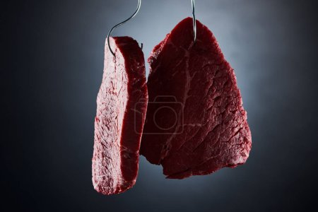 Photo for Raw beef sirloins on metal hooks on dark black background - Royalty Free Image