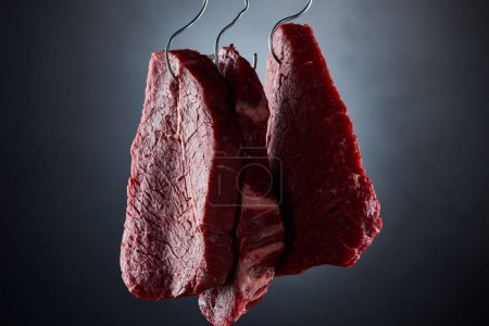 Photo for Raw beef pieces on metal hooks on dark black background - Royalty Free Image