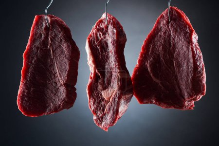Photo for Raw beef steaks on metal hooks on dark black background - Royalty Free Image