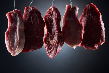 Photo for Assorted raw meat parts on metal hooks on dark black background - Royalty Free Image