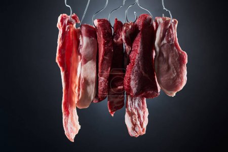 Photo for Assorted raw meat steaks and bacon on metal hooks on dark black background - Royalty Free Image
