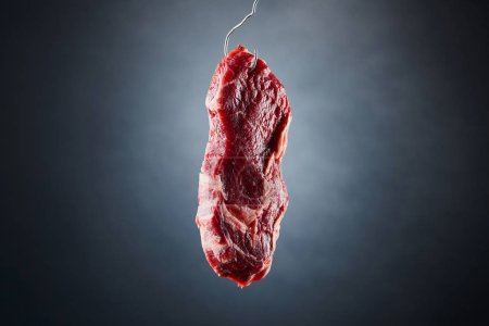 Photo for Raw beef fillet on metal hook on dark black background - Royalty Free Image