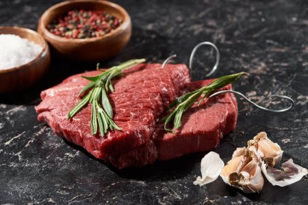 raw beef steak with rosemary near garlic cloves and small bowls with salt and peppercorns on black marble surface